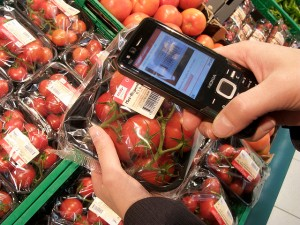 Image of barcode on packaged tomato being scanned in supermarket.
